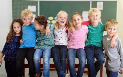 lachende kinder in der grundschule sitzen auf dem tisch